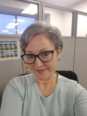 Debbi is rocking a short gray pixie cut, which looks great with her glasses and natural makeup