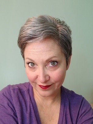 Debbi's short, gray pixie cut is dusted with some copper tones