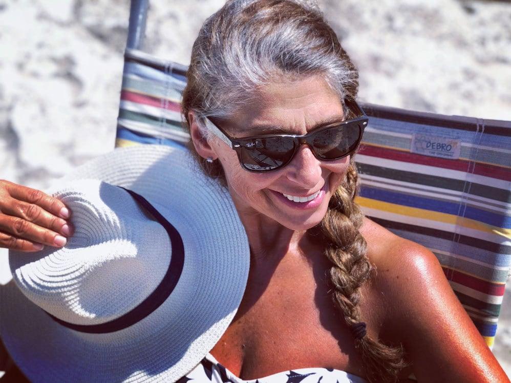 pretty older woman beach gray roots brown braid sunglasses