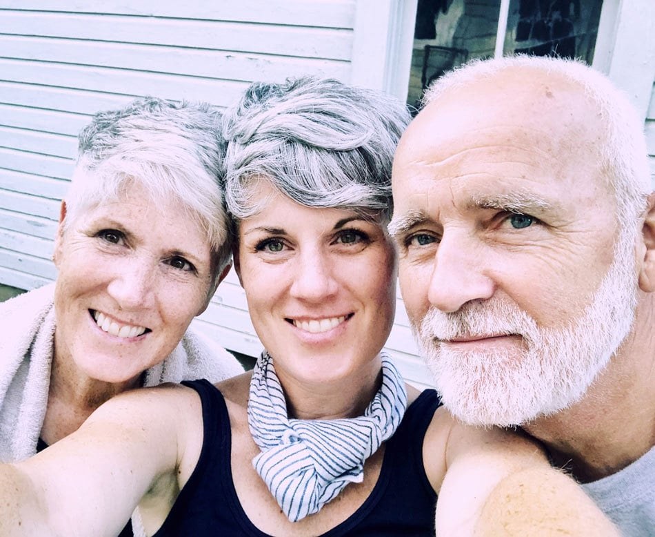 Marci and her silver pixie cut with her parents, both with gray hair.