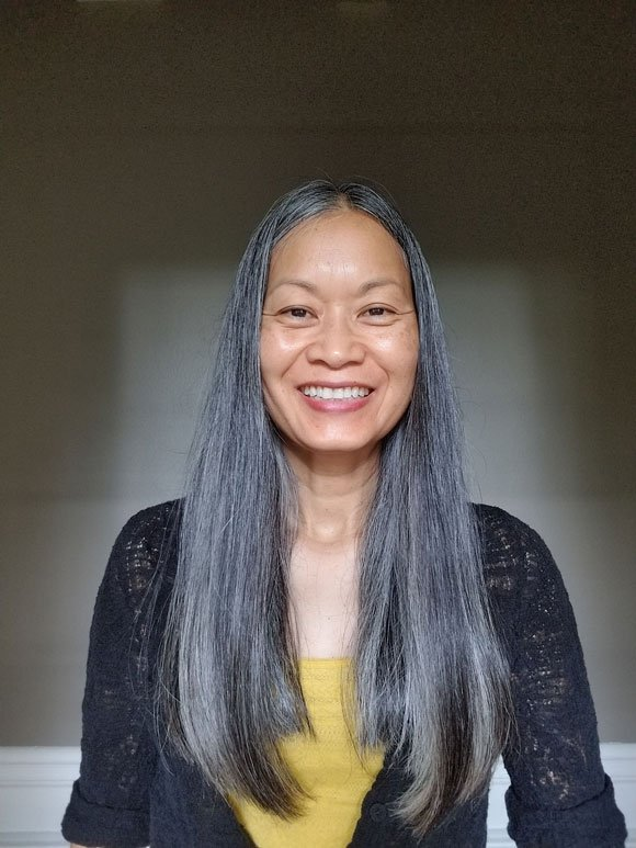 image of Asian woman yellow shirt gray hair