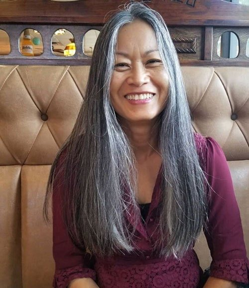 image of pretty woman long gray hair purple shirt