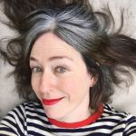 image of woman dark hair gray roots striped sweater gray roots
