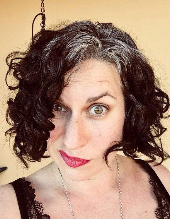 woman black curls hazel eyes gray roots
