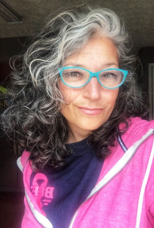 image of woman long gray curly hair blue glasses