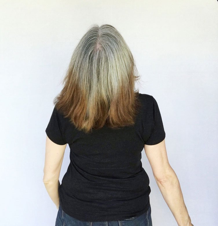 image of woman with gray hair and brassy orange ends one year of going gray