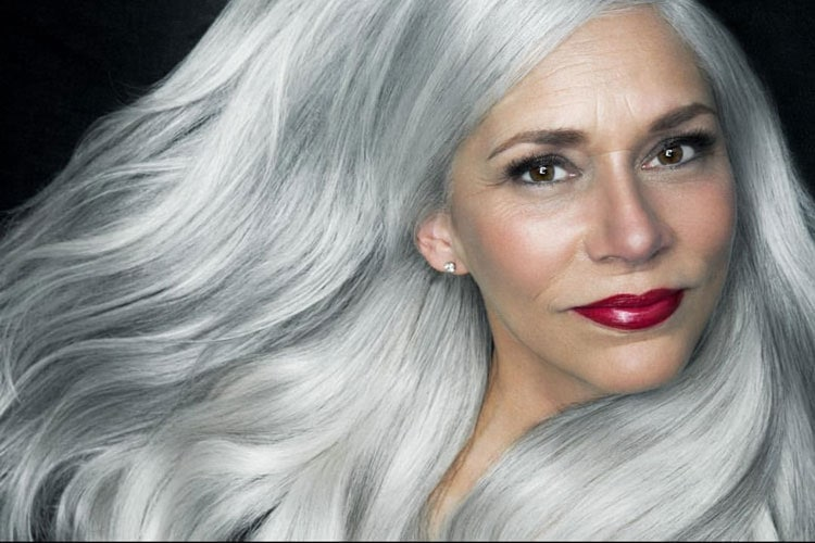Judith models her long and luscious grey hair and rocks a stunning red lip.
