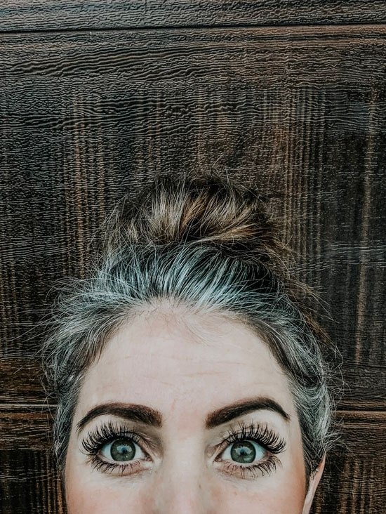 image of woman gray roots and brown bun