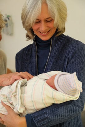 woman with gray hair holding grandchild