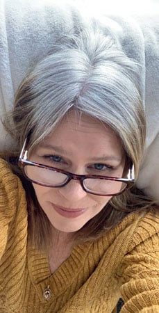 A woman growing out her dyed hair and growing all natural gray hair