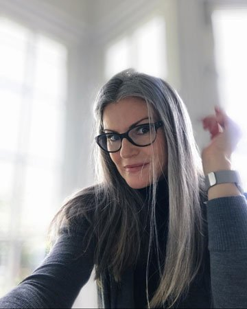image of woman straight gray hair glasses